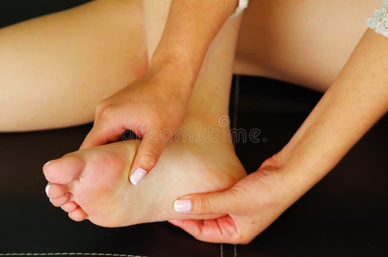 Smärta i foten, auto massage av kvinnlig fot royaltyfri fotografi