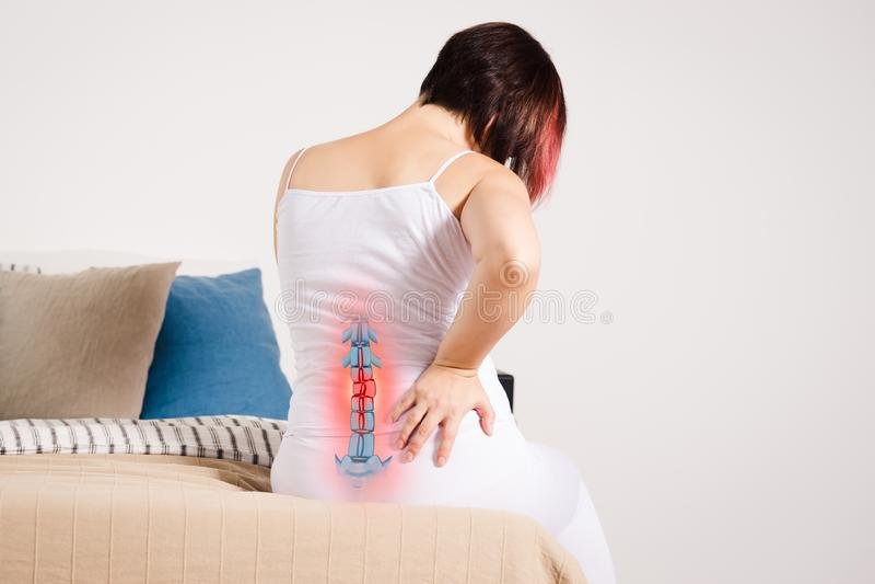 Smärta i ryggen, kvinna med ryggvärk hemma, skadan i den lägre baksidan royaltyfria foton
