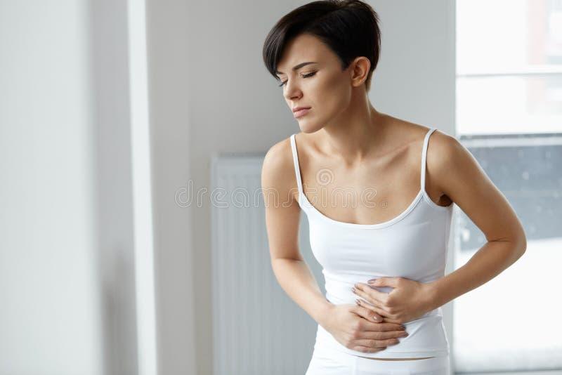 smärta magen Den härliga kvinnan som känner sig buk-, smärtar hälsa arkivfoton