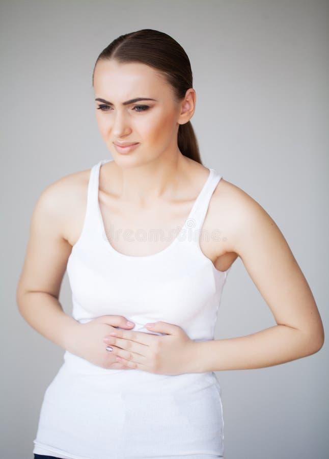 Smärta magen Kvinnan som har smärtsamt magknip, kvinnligt lidande från buk-, smärtar royaltyfria foton