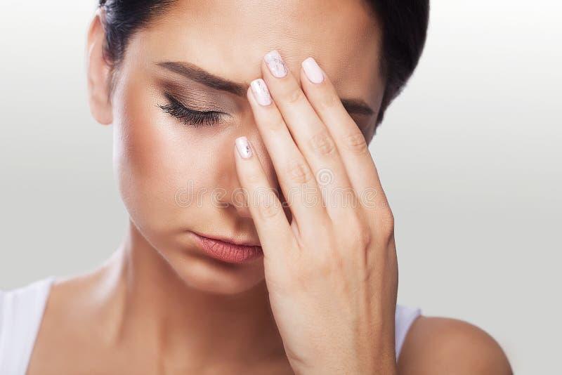 Smärta trött utmattat stressat kvinnalidande från starkt ögonPA arkivbild