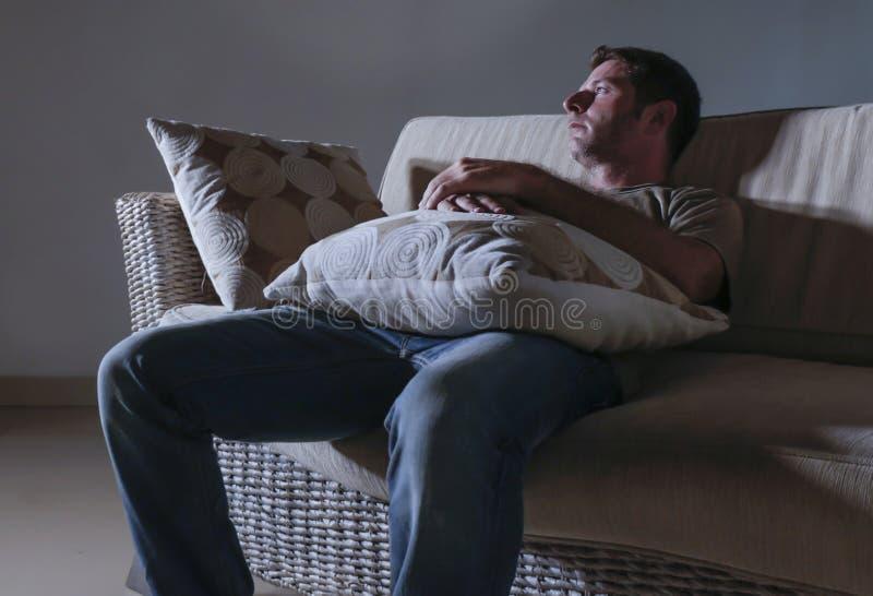 Smärtar den dramatiska ljusa ståenden för livsstilen av ungt ledset och deprimerat mansammanträde på den skuggiga hem- soffan in  royaltyfri bild