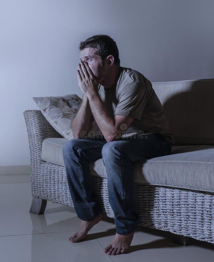 Smärtar den dramatiska ljusa ståenden för livsstilen av ungt ledset och deprimerat mansammanträde på den skuggiga hem- soffan in  royaltyfri fotografi