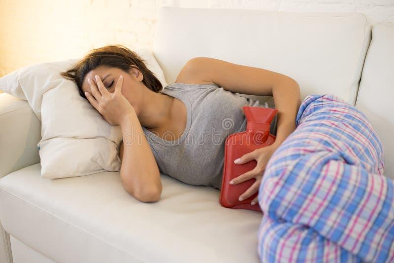 Smärtar den hållande varmvattenflaskan för den unga härliga latinamerikanska kvinnan mot buken som lider menstruations- period royaltyfria bilder
