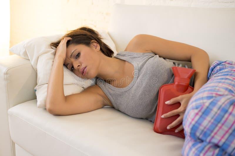 Smärtar den hållande varmvattenflaskan för den unga härliga latinamerikanska kvinnan mot buken som lider menstruations- period arkivbilder