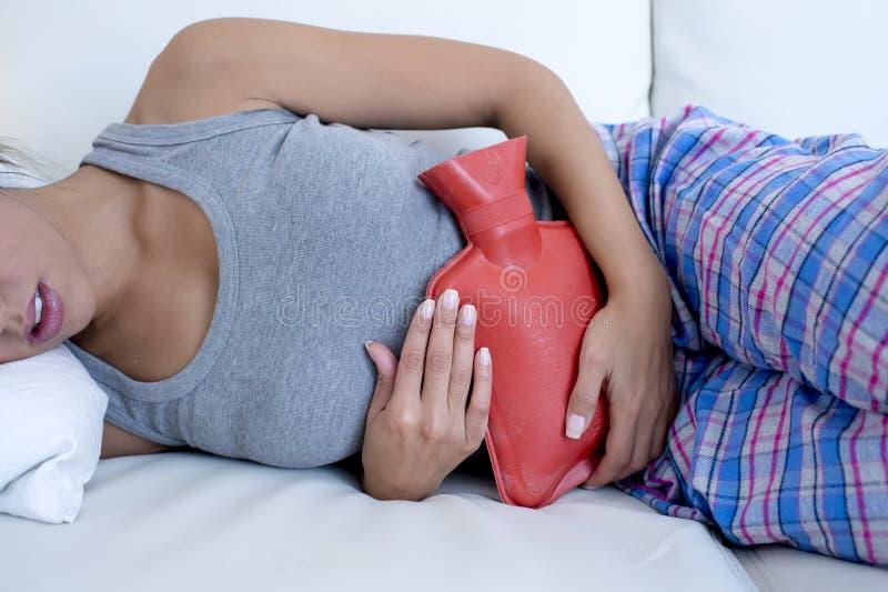 Smärtar den hållande varmvattenflaskan för den unga härliga latinamerikanska kvinnan mot buken som lider menstruations- period arkivfoton