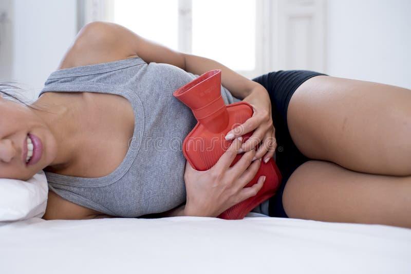 Smärtar den hållande varmvattenflaskan för den unga härliga latinamerikanska kvinnan mot buken som lider menstruations- period arkivfoto