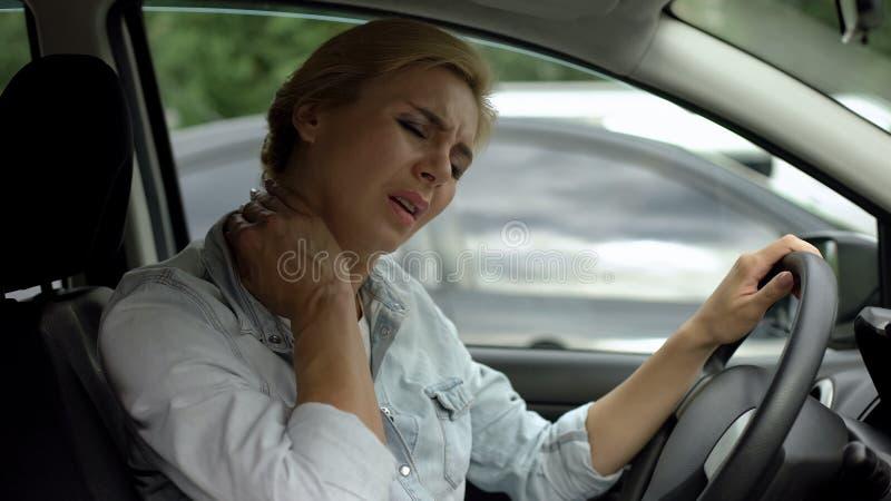 Smärtar den känsliga halsen för den kvinnliga chauffören, inflammation för den tillbaka muskeln, stillasittande livsstil royaltyfri bild