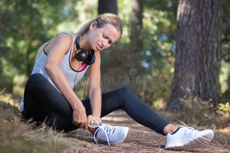 Smärtar den rörande foten för den kvinnliga löparen in tack vare den stukade ankeln fotografering för bildbyråer