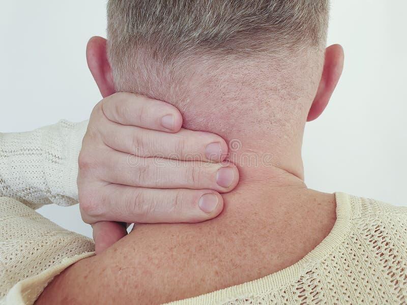 Smärtar den ryggrads- vuxna öm halsen för mannen att massera sjukdomspänningsscoliosis som lider inflammation arkivbilder