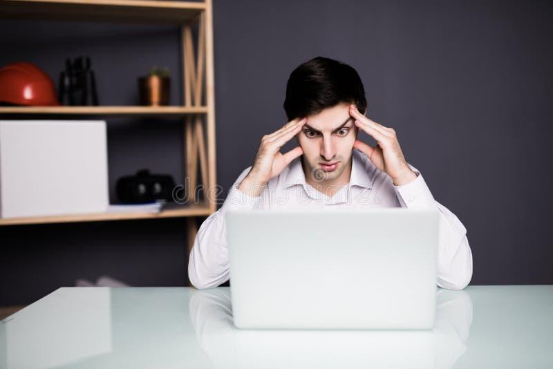 Smärtar gör ont det funktionsdugliga problemet för affärsmannen genom att använda bärbara datorn som ser skärmen, hållhuvudhand,  arkivfoton
