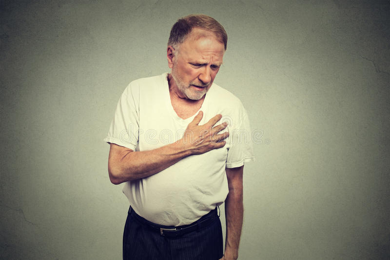 Smärtar moget manlidande för pensionären från bad i hans bröstkorghjärtinfarkt royaltyfri bild