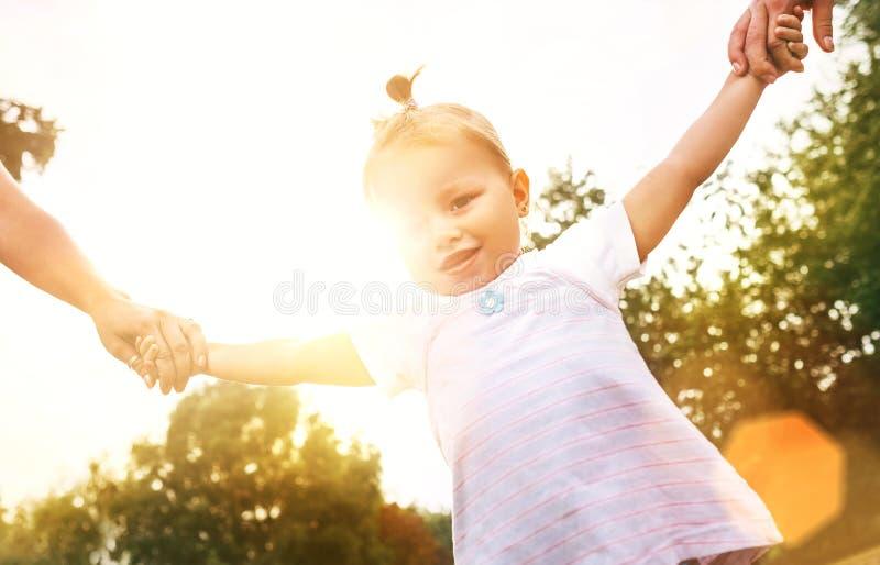 Små 2 år gammal flicka som går med föräldrar som rymmer deras händer royaltyfria foton
