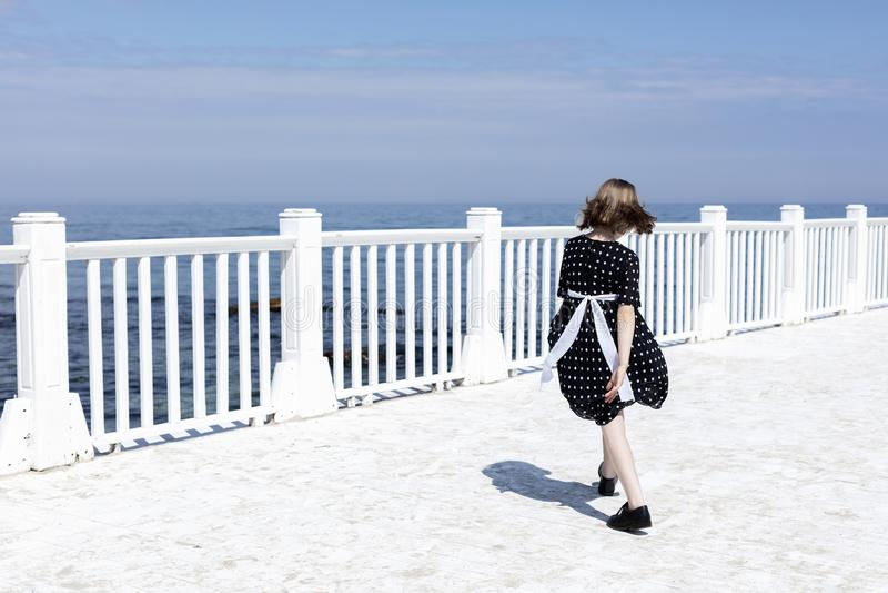 Små 7 år gammal nätt gladlynt flicka i en svart klänning med vita prickar står på en trävit pir arkivbild