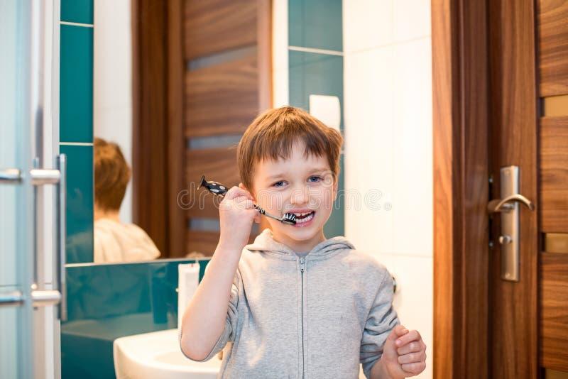 Små 7 år gammal pojke som borstar hans tänder royaltyfria bilder