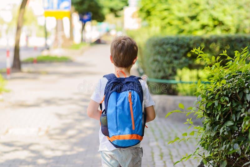 Små 7 år skolpojke som går till skolan fotografering för bildbyråer