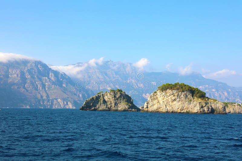 Små öar i mitt av det blåa havet, sikt från skeppet nära den Amalfi kusten, Italien arkivfoton