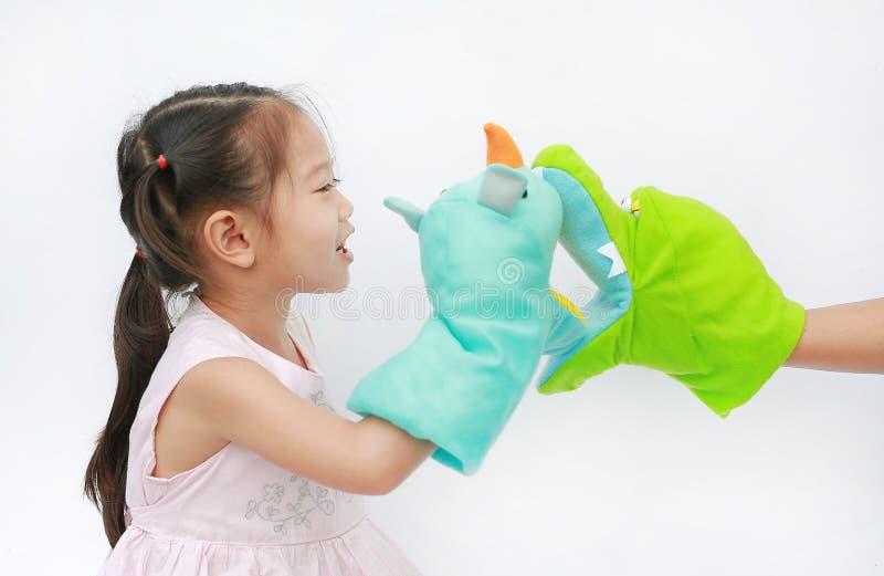 Små asiatiska barnflickahänder som spelar djura dockor med handen av hennes moder på vit bakgrund Utbildningsbegrepp royaltyfri fotografi