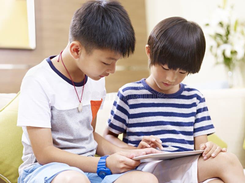 Små asiatiska bröder som tillsammans använder den digitala minnestavlan royaltyfria foton
