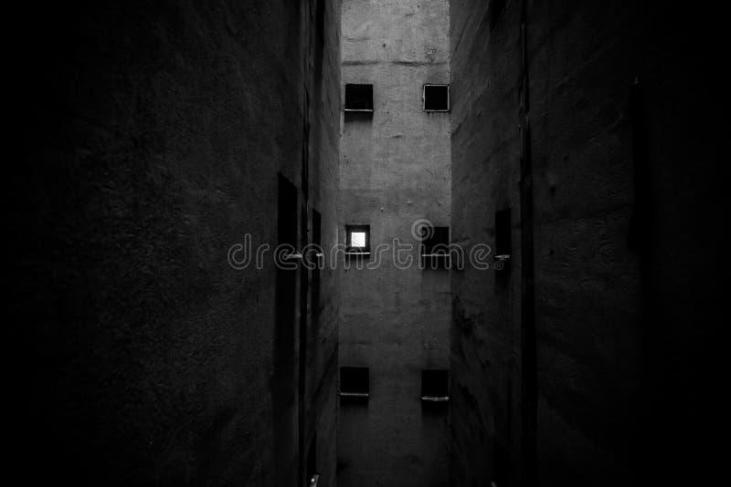 Små badrumfönster i en grop för luftlufthål inom ett högväxt kommunistiskt eraflerbostadshus royaltyfri bild
