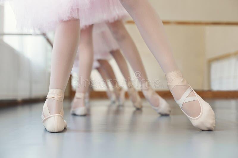 Små ballerina som utbildar benposition på balettgrupp, kopieringsutrymme fotografering för bildbyråer