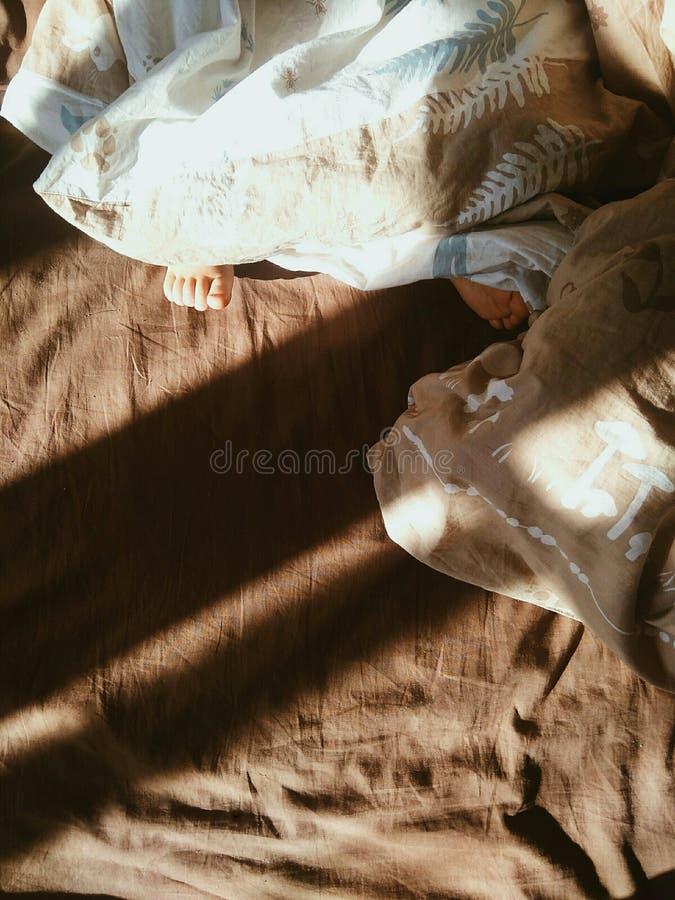 Små barn foots på sängen royaltyfri fotografi