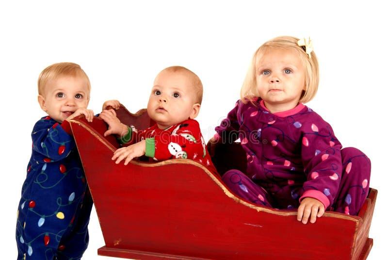 Små barn i julpyjamas som sitter i en släde arkivfoto