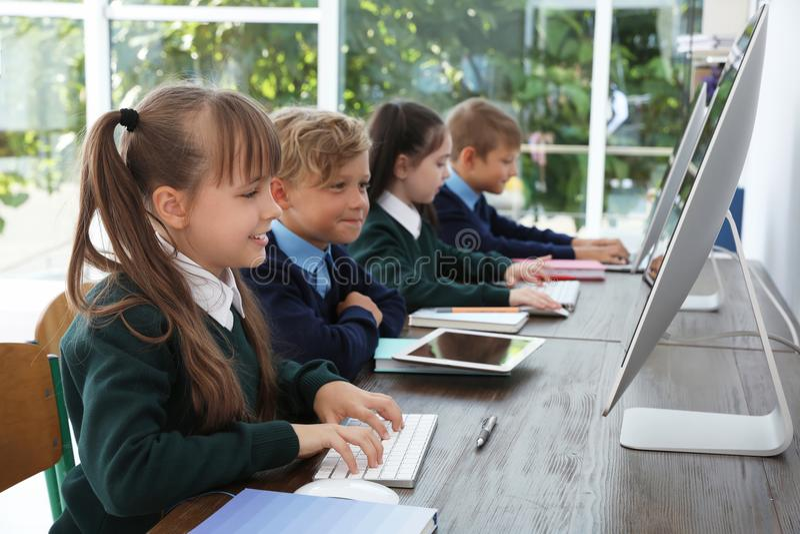 Små barn i stilfull skolalikformig på skrivbord royaltyfria foton