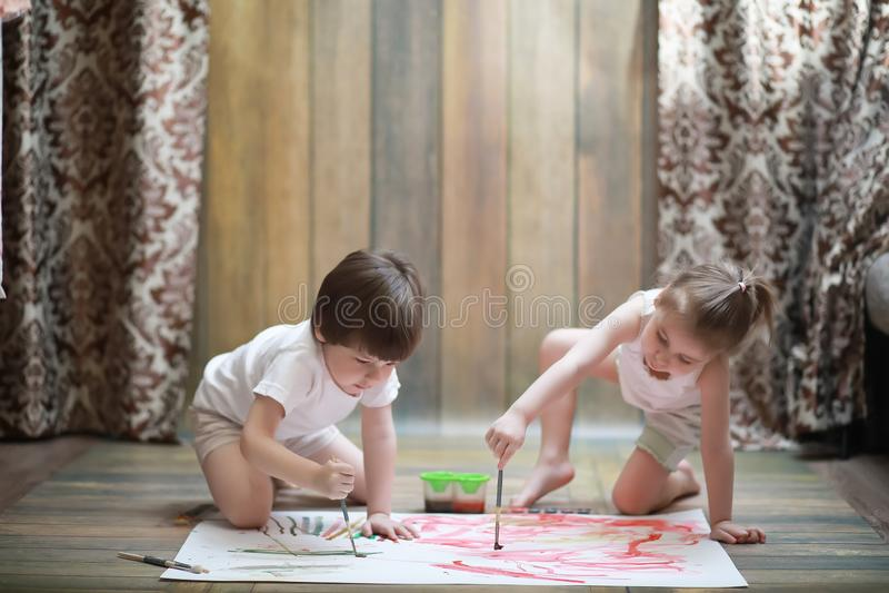 Små barn målar på ett stort ark av papper arkivfoto