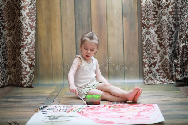 Små barn målar på ett stort ark av papper royaltyfria bilder