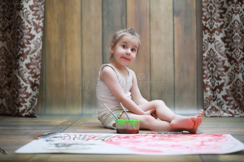 Små barn målar på ett stort ark av papper royaltyfri bild
