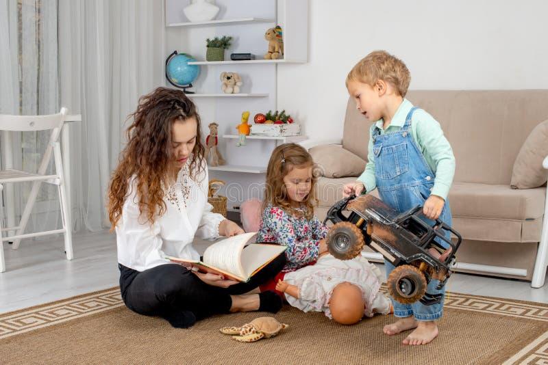 Små barn med en barnflicka eller med en ung moder eller med en t arkivbild
