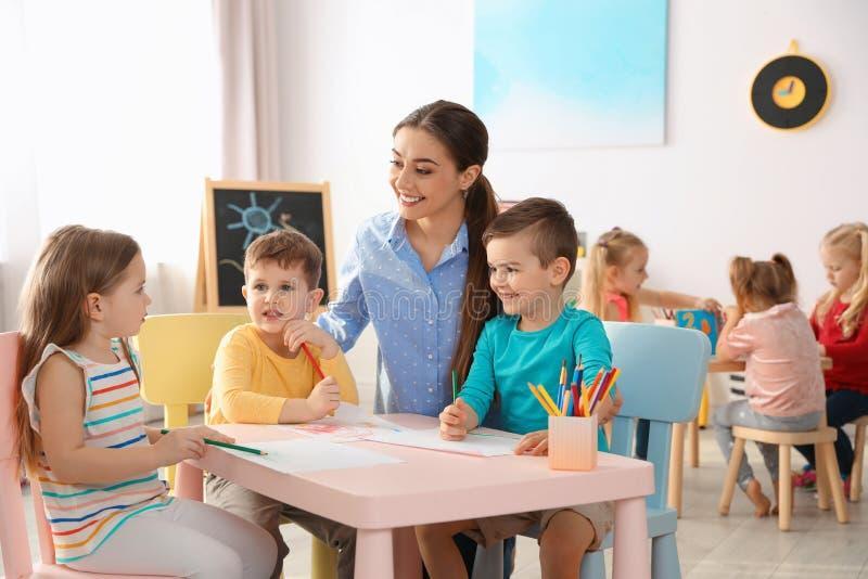 Små barn med teckningen för dagislärare på tabellen inomhus fotografering för bildbyråer