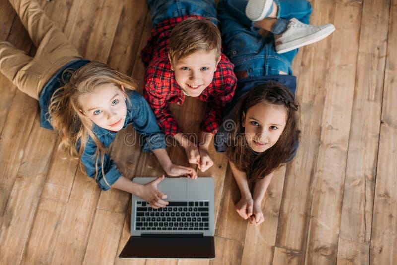 Små barn som hemma använder den digitala bärbara datorn royaltyfri foto