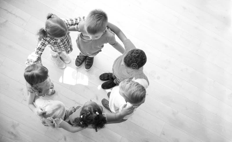 Små barn som inomhus gör cirkeln med händer runt om de, bästa sikt royaltyfri foto