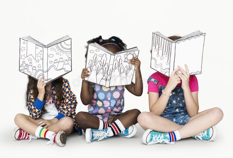 Små barn som läser berättelseböcker arkivfoton