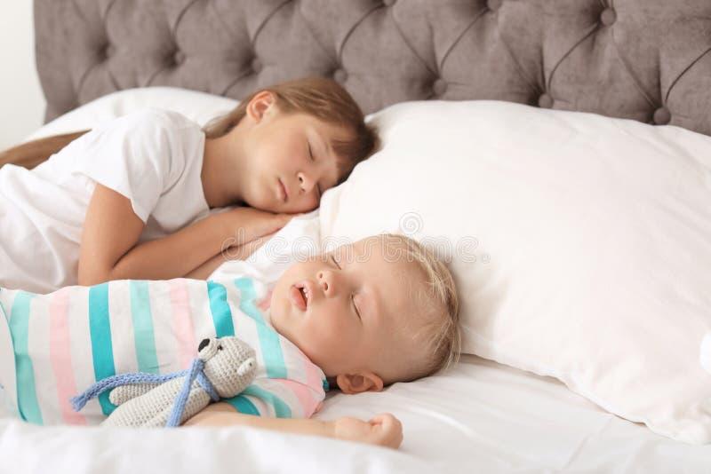 Små barn som sover i säng royaltyfria bilder