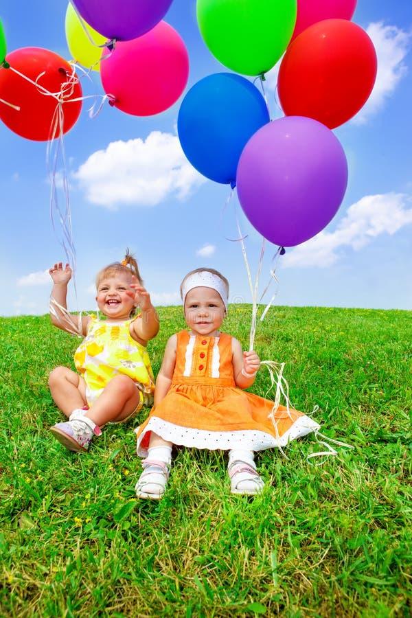 Små barn som spelar med ballonger arkivfoton
