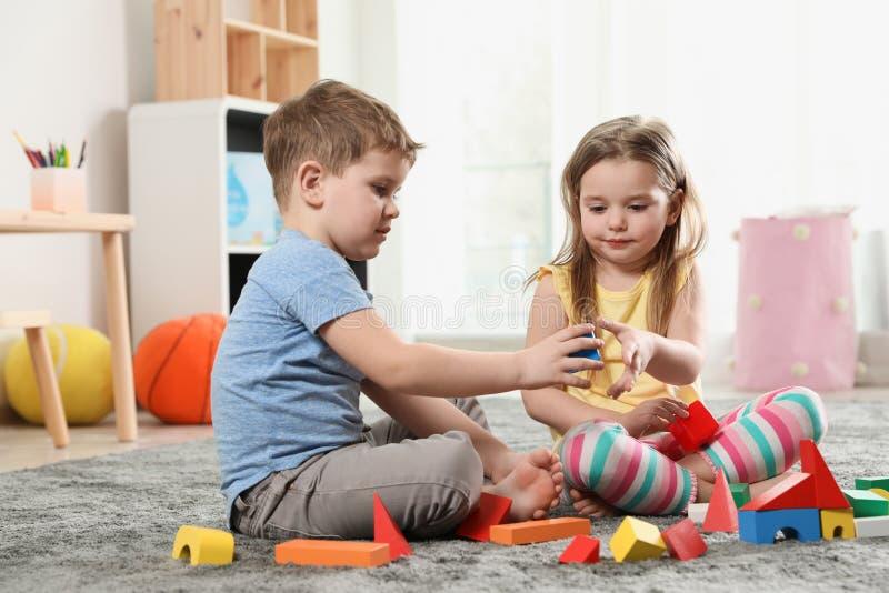 Små barn som spelar med färgrika kvarter royaltyfri foto