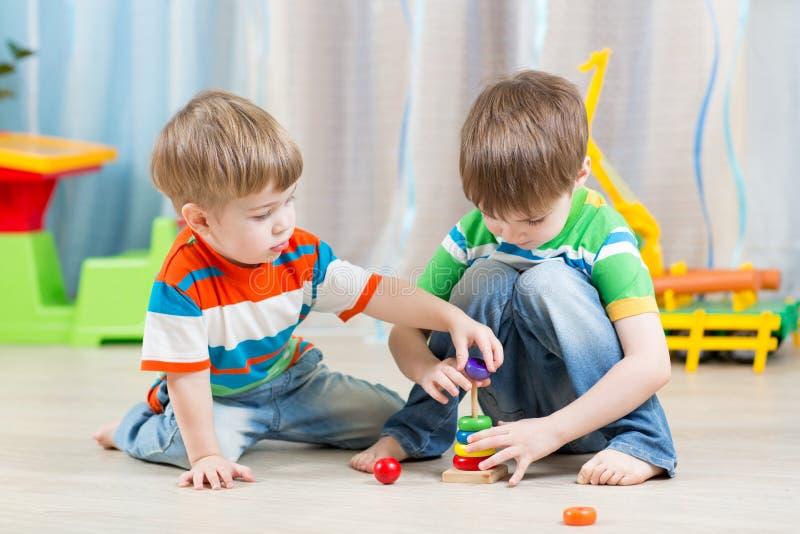 Små barn som spelar med leksaker arkivbilder