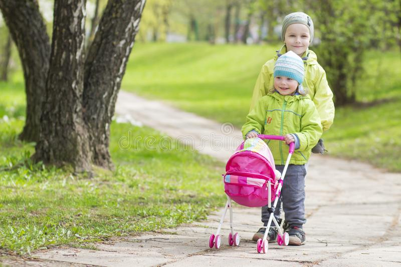 Små barn som syskongruppen kör en leksakbarnvagn parkerar in arkivfoto