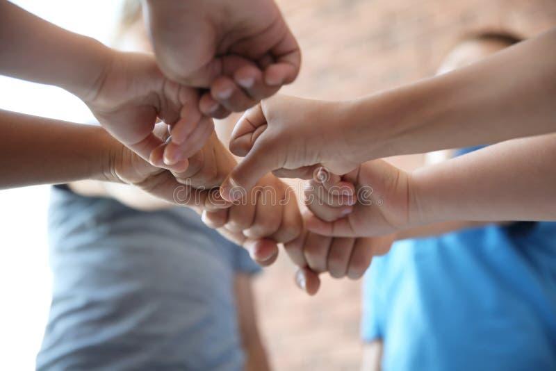 Små barn som tillsammans sätter deras händer arkivbild