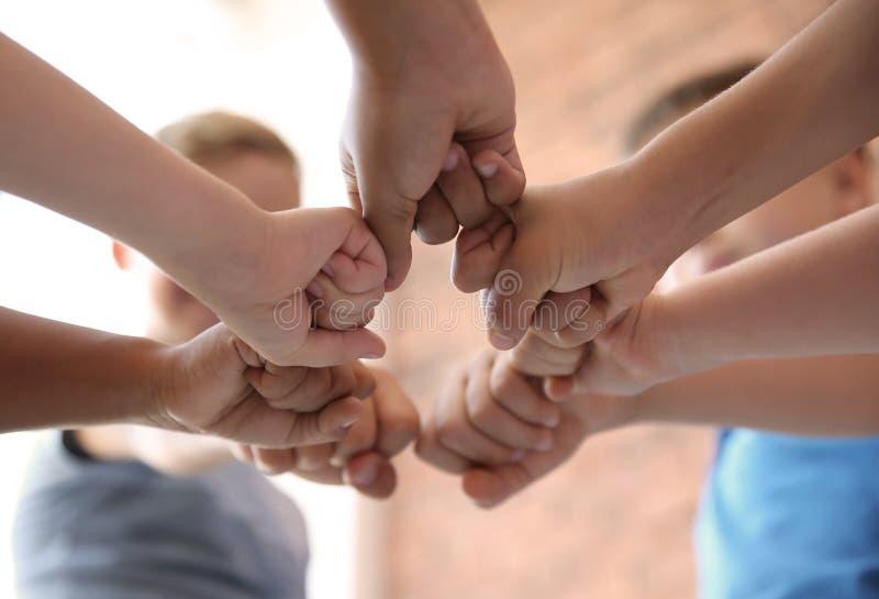 Små barn som tillsammans sätter deras händer royaltyfri fotografi