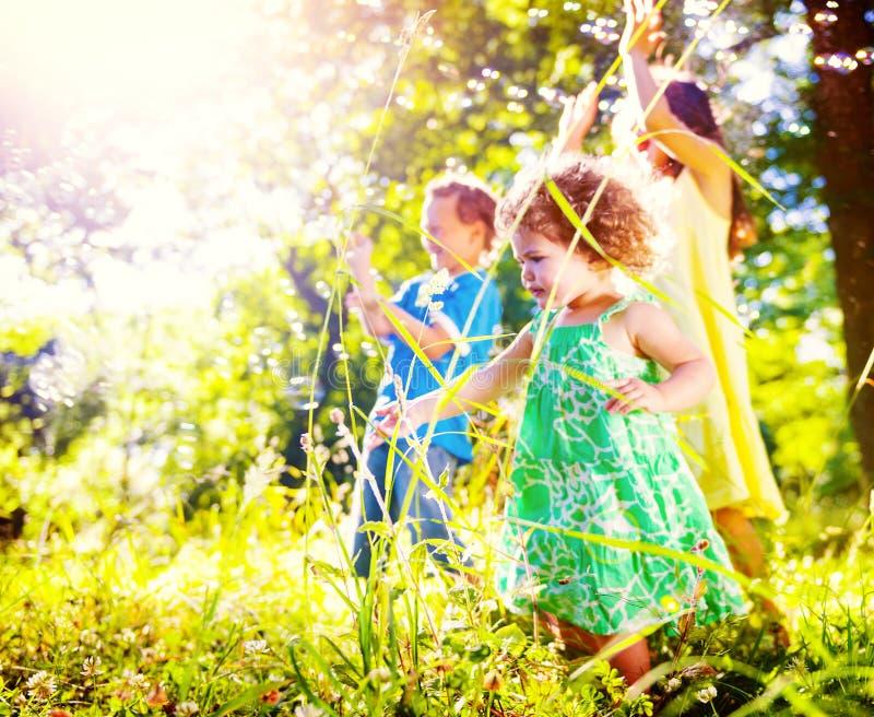 Små barn som tillsammans utomhus spelar begrepp arkivbilder