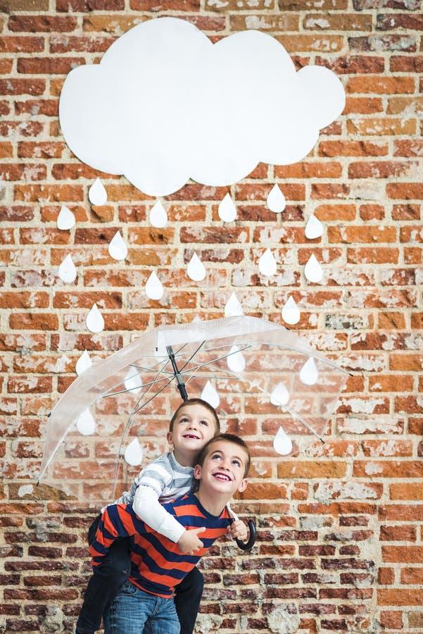Små barn under vita pappregndroppar royaltyfri bild