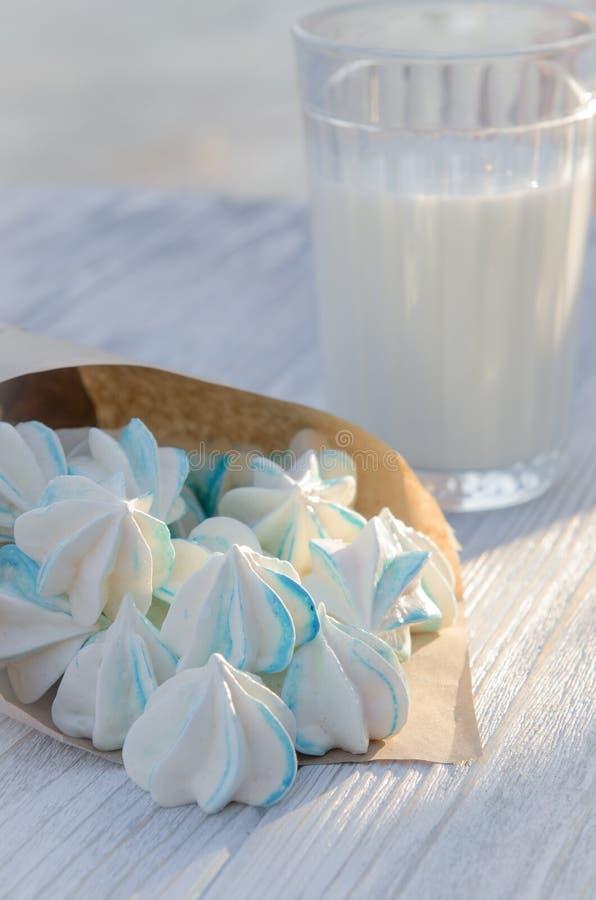 Små blåa sockerkakor och ett exponeringsglas av mjölkar royaltyfri bild