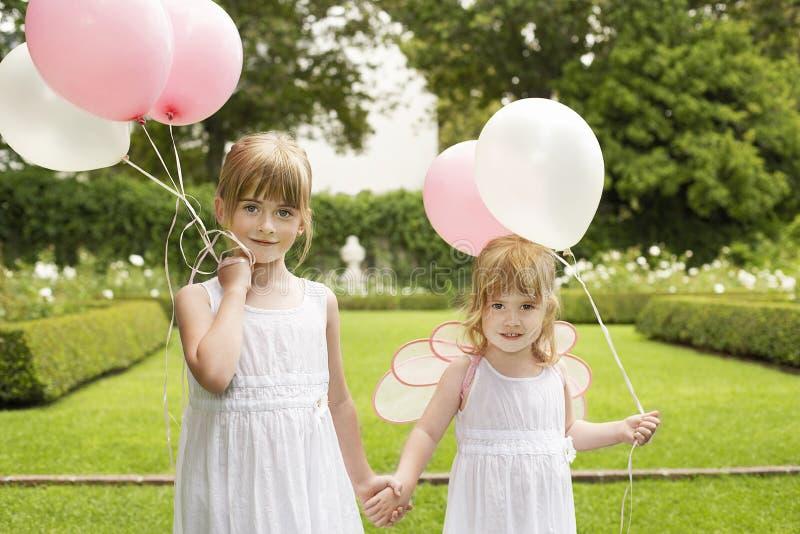 Små brudtärnor som rymmer ballonger i trädgård arkivfoto