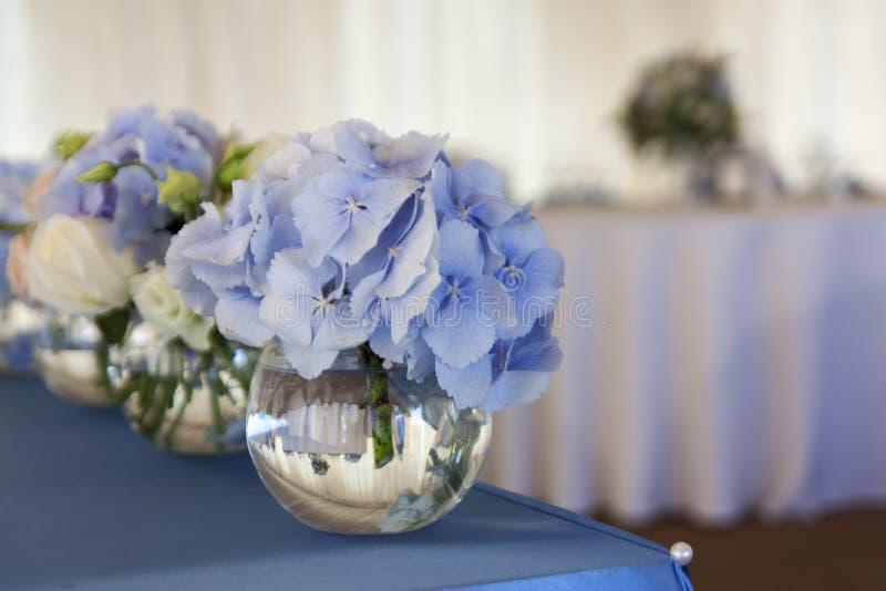 Små buketter av blommor i exponeringsglasvaser är på den festliga tabellen royaltyfria foton