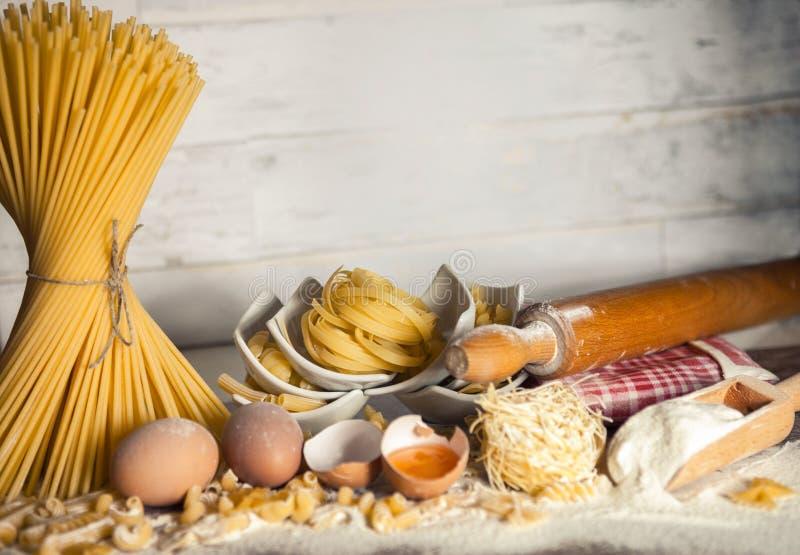Små bunkar med pasta med kavlen, bunden spagetti och mjöl royaltyfri fotografi