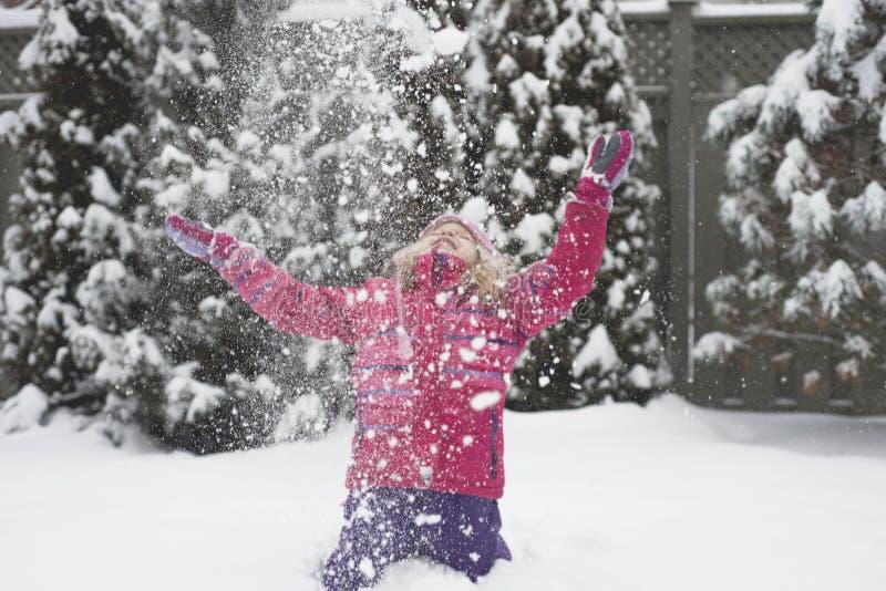 Små Caucasian blonda flickor i rött omslag spelar med snö på gran-träd suddighetsbakgrund royaltyfri bild